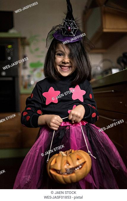 Portrait of little girl dressed up as a witch at Halloween