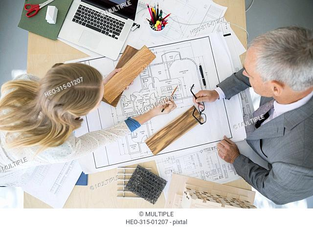Overhead view architects discussing blueprints