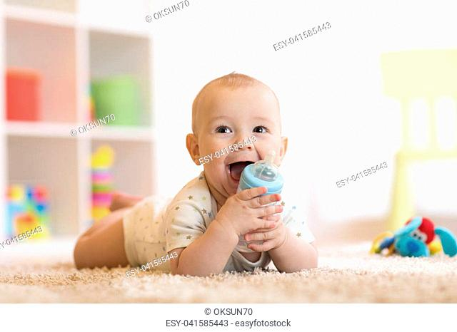 Pretty baby boy drinking water from bottle. Kid lying on carpet in nursery at home. Smiling child is 7 months old