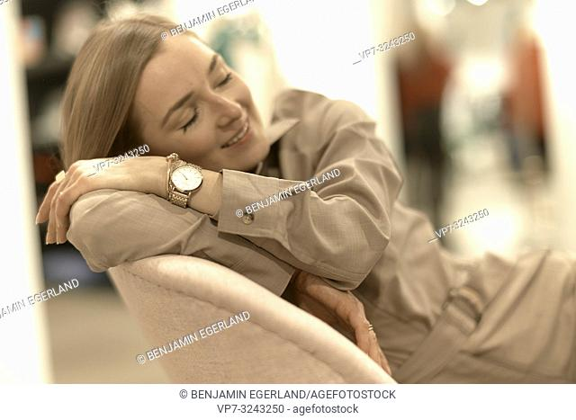 fashionable woman relaxing in armchair, in Munich, Germany