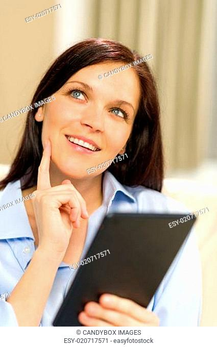 Pensive cheerful woman holding digital tablet