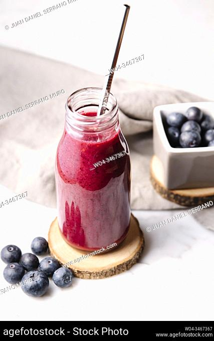 Smoothie in a glass bottle, metal straw and blueberries over a slice of wood. High angle shot