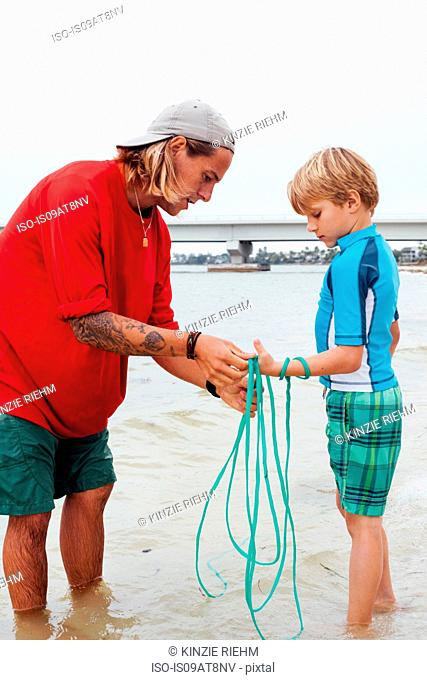 Teacher showing boy how to use cast net, Sanibel Island, Pine Island Sound, Florida, USA