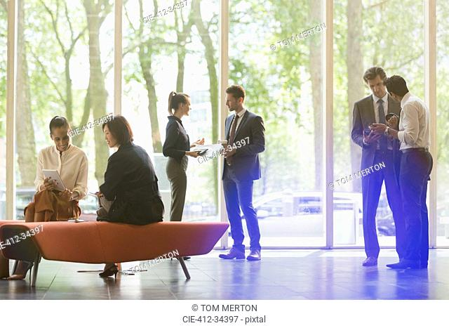 Business people talking and working in office lobby