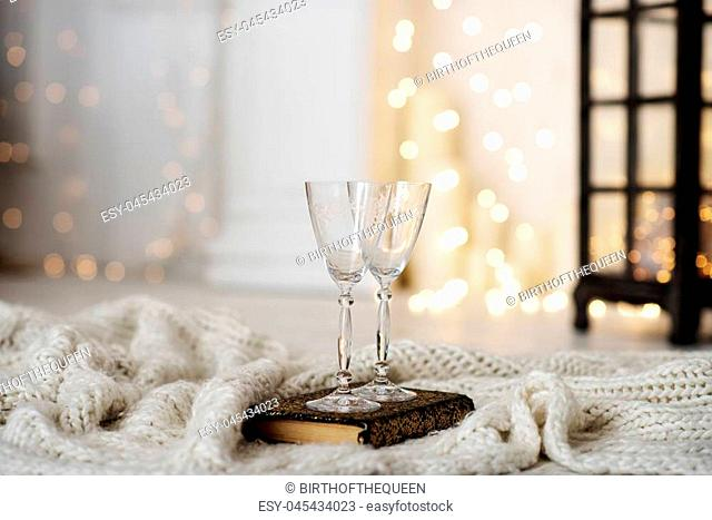 Beautiful two glasses of champagne standing on the table in the background of a blurred room with a decorated Christmas tree and fireplace. Soft focus