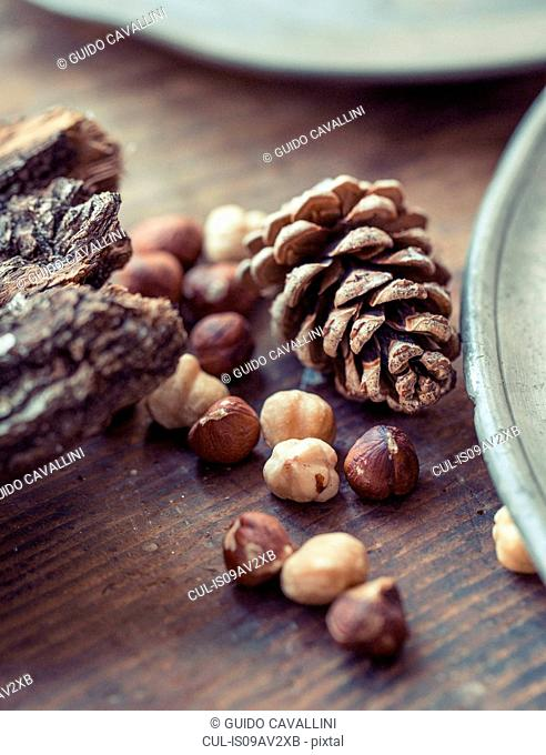 Cropped close up view of hazelnuts and pinecones on wooden surface