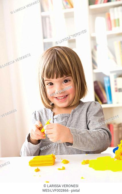 Portrait of happy little girl playing with yellow modeling clay