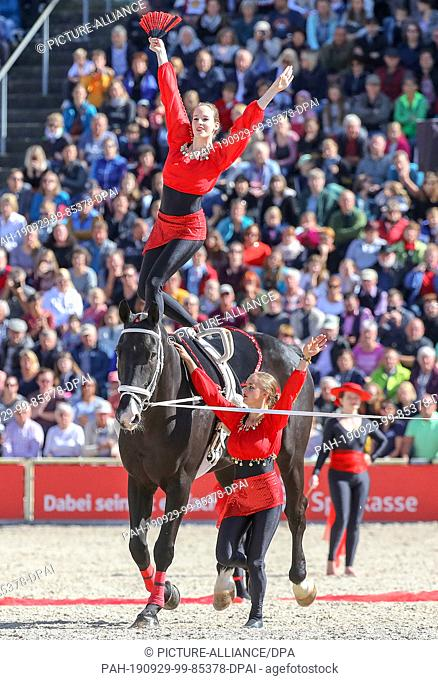 """29 September 2019, Baden-Wuerttemberg, Gomadingen-Marbach: During the 2019 Stallion Parade, girls from a vaulting group will be riding a horse in the """"""""Spain""""""""..."""
