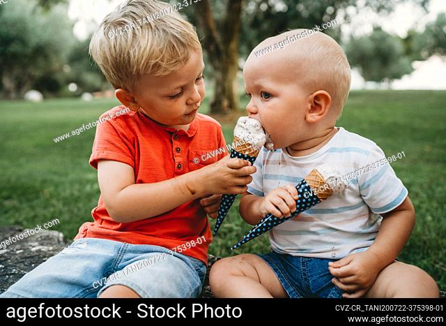 Big brother sharing his ice cream cone with his baby sibling