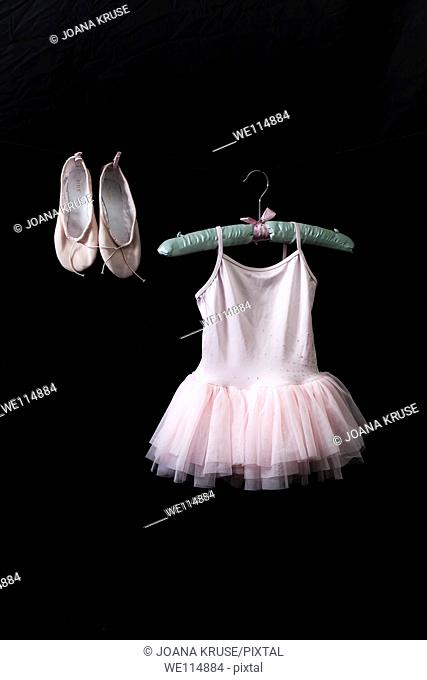 Ballet dress on a satin hanger with ballet shoes