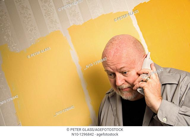 Balding, middle-age man talking on the telephone