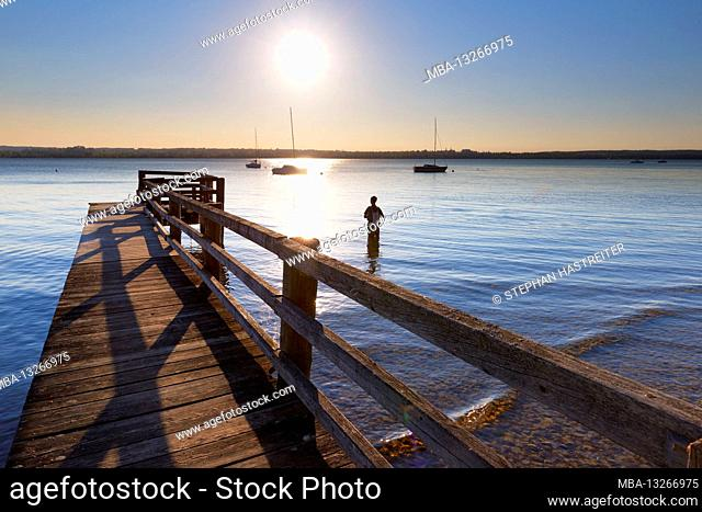 Evening mood at the Ammersee with angler and jetty