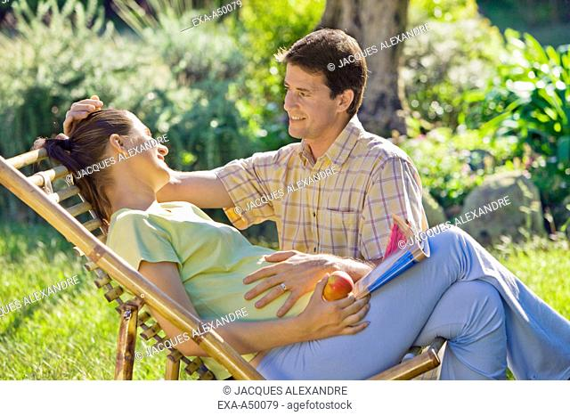 Young pregnant woman relaxing together with her husband in the garden on a warm summers day