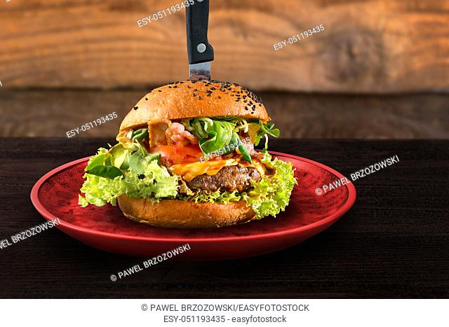 Original served beef burger on red plate with knife. Wooden table background. Fast food restaurant design concept