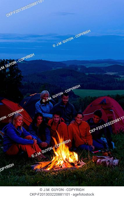 Friends watching fire together beside camp and tents in dark