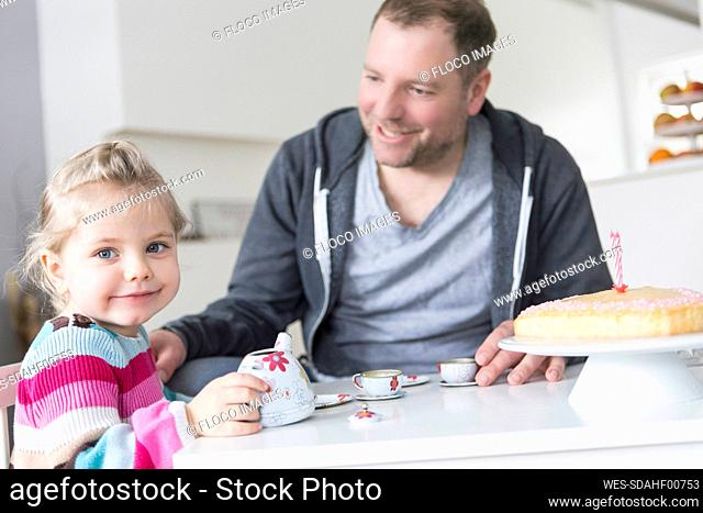 Father and daughter playing with doll's china set