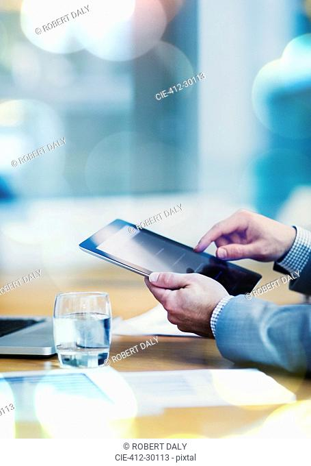 Businessman using digital tablet at conference table