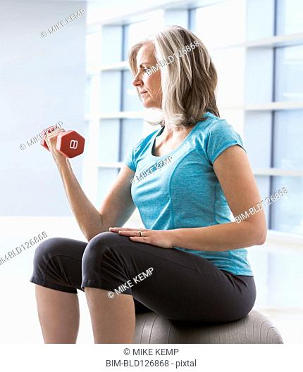 Caucasian woman doing biceps curls with dumbbell