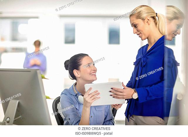 Two young female office workers with digital tablet at desk