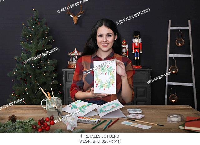 Portrait of smiling young woman showing her painted Christmas card