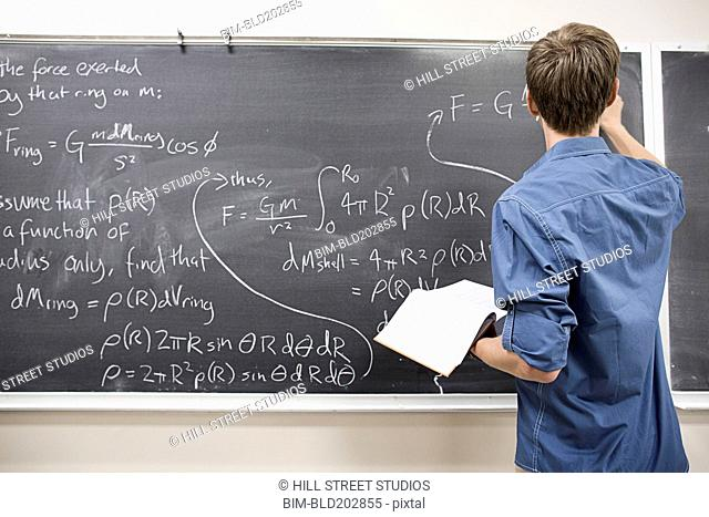 Caucasian student writing on blackboard