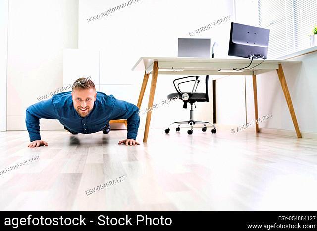Businessman Doing Push Up On Hardwood Floor In Office