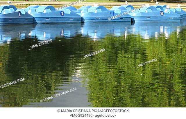 Blue boats reflection on a boating lake in Battersea Park, London, UK
