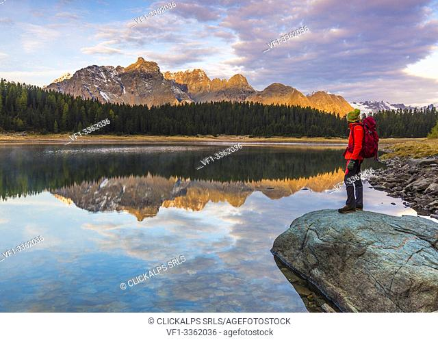 Hiker admiring sunrise from the shore of Lake Palù, Malenco Valley, Valtellina, Sondrio province, Lombardy, Italy