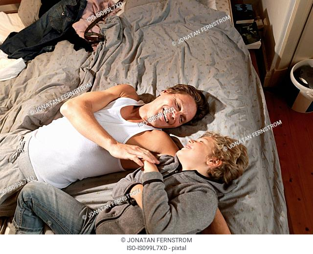 Mature man and son relaxing on bed