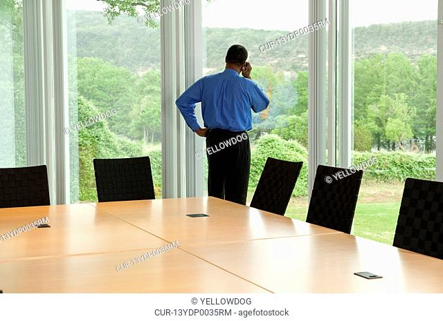 businessman standing at window of conference room talking on phone and looking outside