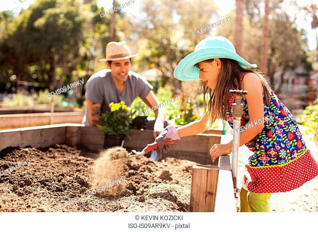 Enthusiastic girl digging flower bed in community garden