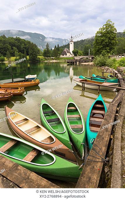 Lake Bohinj (Bohinjsko jezero), Triglav National Park, Upper Carniola, Slovenia. Canoes for rent. The church of St. John (Cerkev sv Janeza) at Ribcev Laz in...