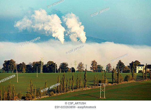 smoking chimneys in from factory hidden in mist