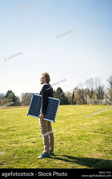 Male entrepreneur holding solar panel while looking away at park on sunny day