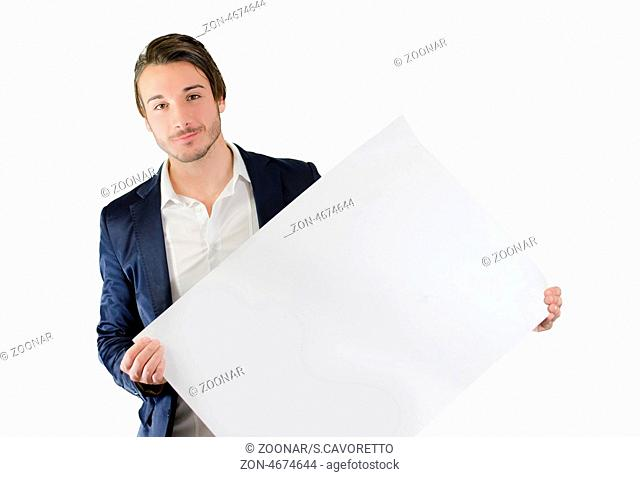 Attractive young man holding and showing empty, blank white board, sign or paper sheet