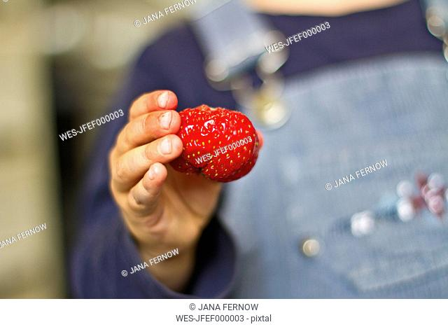 Girl holding strawberry in her hand, close up