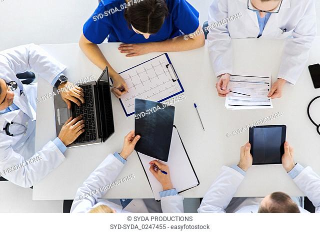 doctors with x-ray and cardiogram at hospital