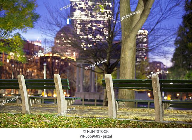 Park bench with buildings lit up at dusk, Boston, Massachusetts, USA
