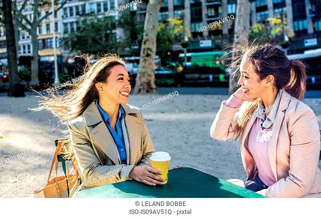 Young adult female twins talking and drinking coffee in city park