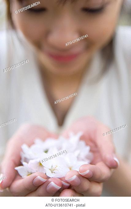 Woman scooping up cherry flowers with hands, smiling, front view, close up, differential focus, Japan