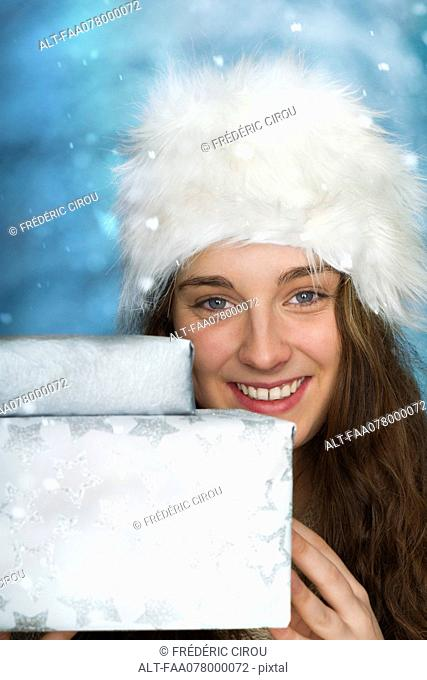 Young woman holding Christmas presents, portrait