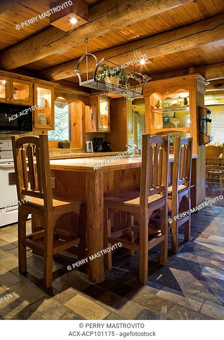 Island with wooden high-back chairs in the kitchen inside a Scandinavian cottage style log home, Quebec, Canada. This image is property released