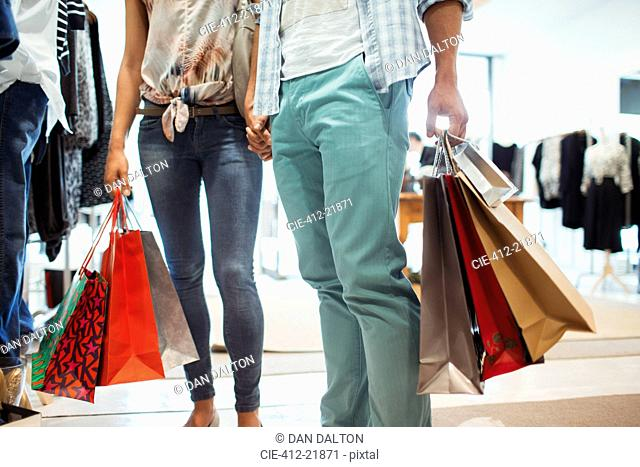 Couple carrying shopping bags in clothing store