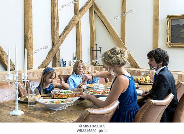 Caucasian family eating dinner in dining room