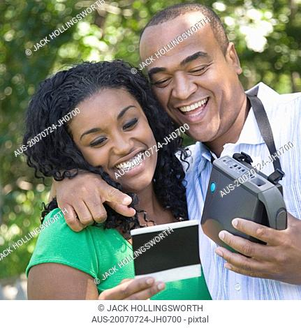 Close-up of a young woman and a mid adult man looking at a photograph