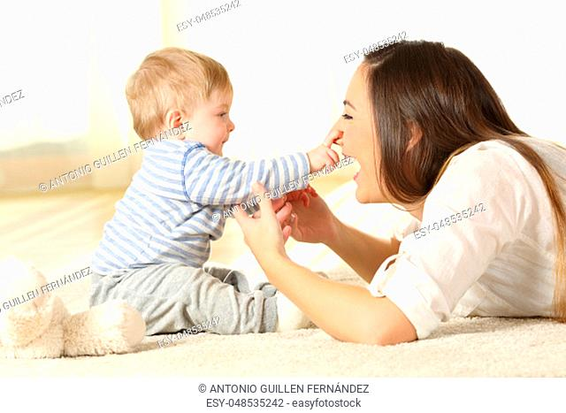 Happy baby touching his mother face lying on a carpet at home