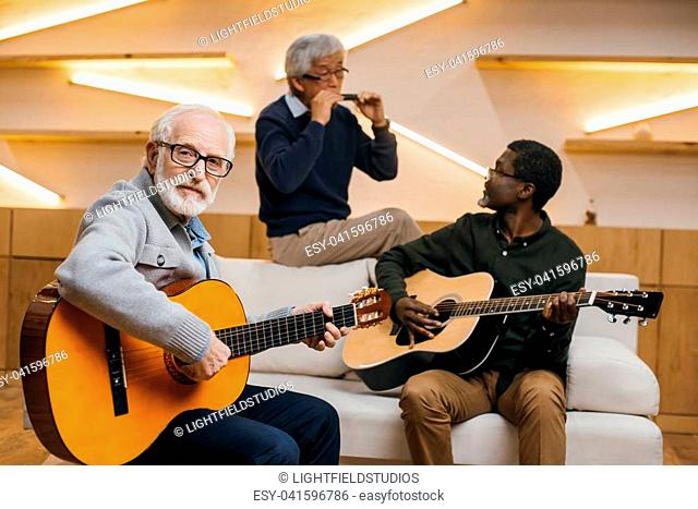 group of handsome senior friends playing music with guitars and harmonica