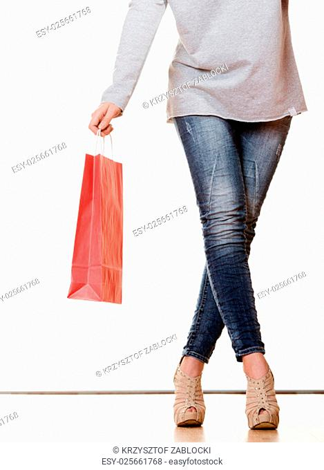 buying retail sale concept. fashionable woman denim pants legs high heels shoes with red shopping bag isolated on white
