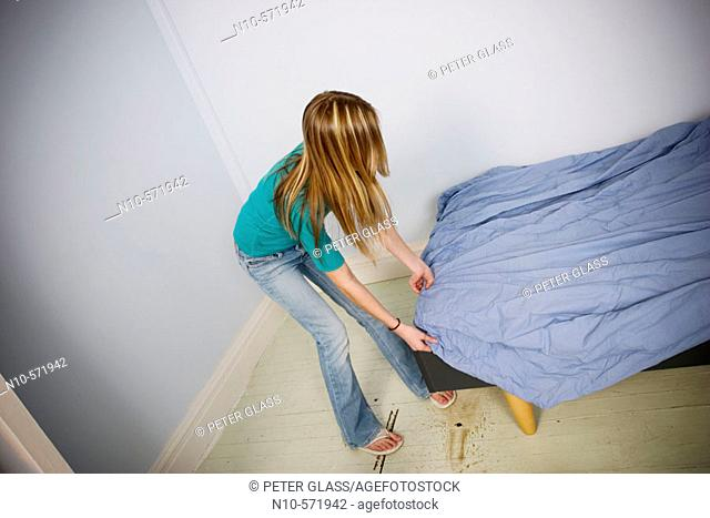 Long blond-hair teen girl putting a sheet onto a bed