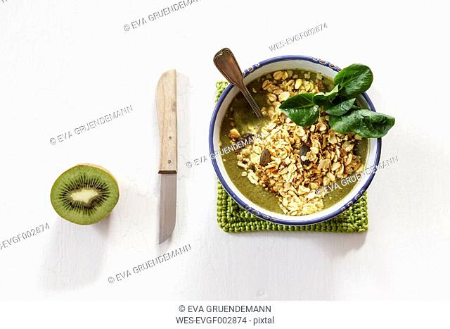 Bowl of green smoothie with mix of oatflakes and granola, kitchen knife and half of kiwi